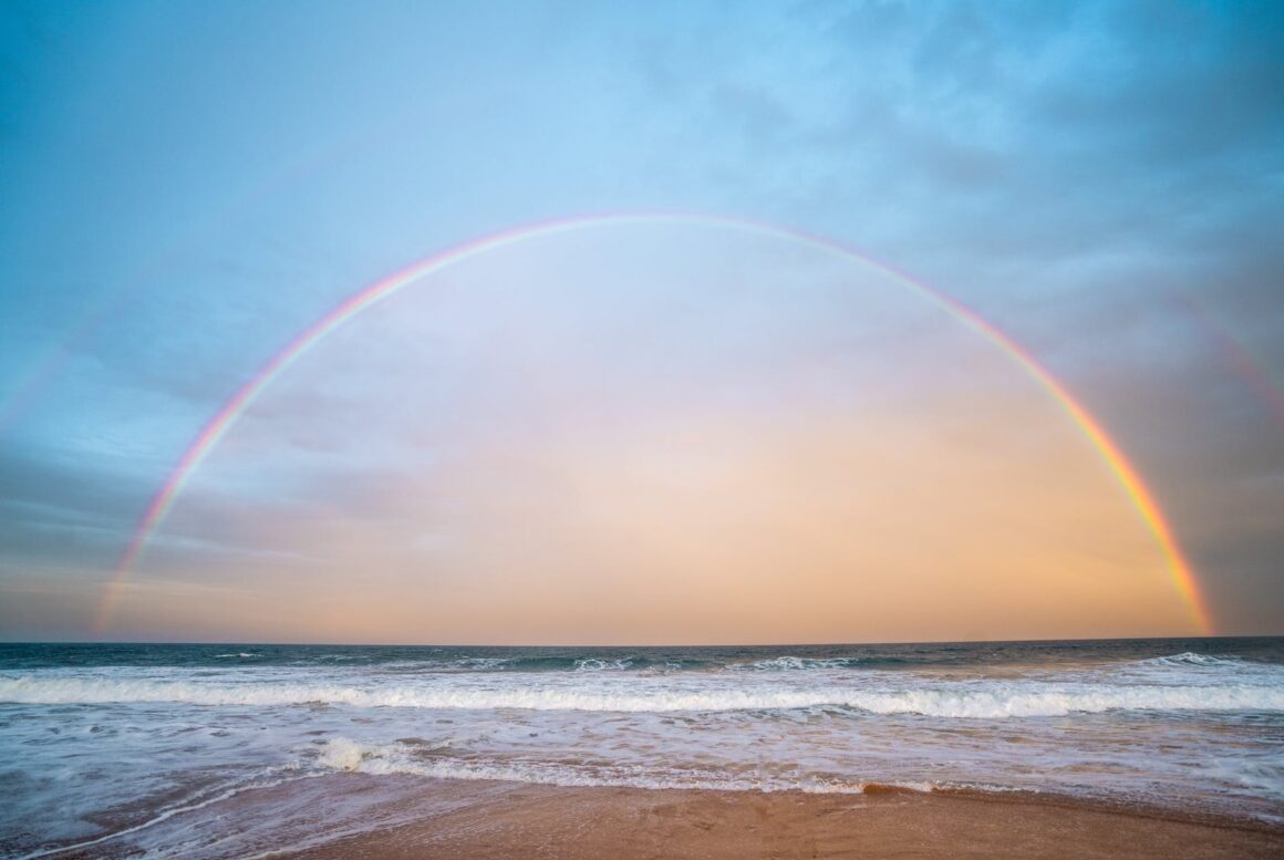 rainbow over rippling sea in nature